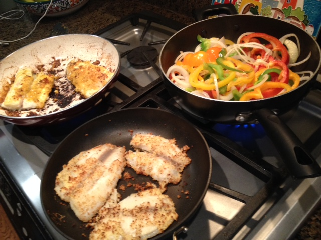 My mix and match fish dinner cooking away, walleye in the white pan, tilapia in the black with peppers and onions in the third.