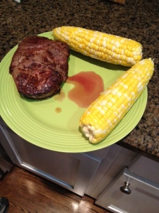 A cooked ribeye with corn