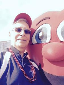 Me with the heart mascot, sporting my survivor's cap and beads for each year since my 2012 surgery.